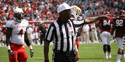 An NFL referree points to the end zone of a team that has committed a penalty. find a job with the NFL with Jobs in Sports.
