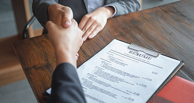A Sports Job applicant and an Interviewer shake hands above a resume, which rests on a stained wood table.