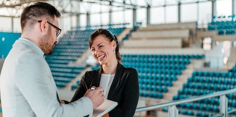 Sports marketing professionals stand in a stadium and laugh in enjoyment as they stand in an arena planning an event.